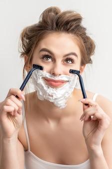 Mulher jovem e bonita caucasiana sorridente barbeando o rosto com navalha, olhando para cima no fundo branco