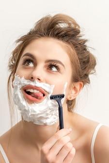 Mulher jovem e bonita caucasiana sorridente barbeando o rosto com uma lâmina de barbear enfiando a língua para fora, olhando para o fundo branco