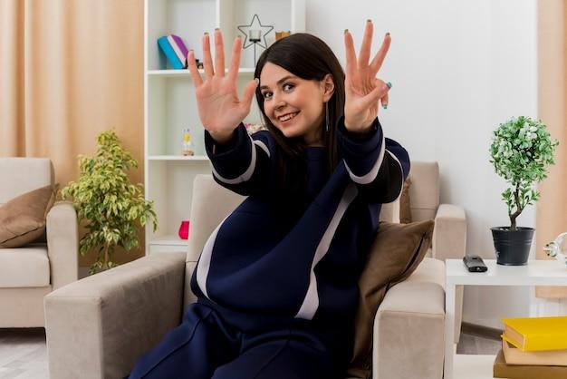 Mulher jovem e bonita caucasiana sorridente, sentada em uma poltrona em uma sala projetada, mostrando cinco e três com as mãos