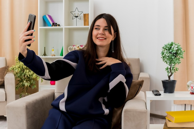 Mulher jovem e bonita caucasiana sorridente, sentada na poltrona na sala projetada, tocando no peito e tomando selfie