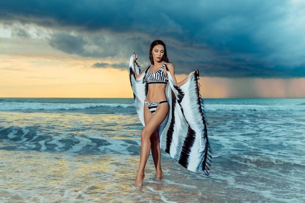 Mulher jovem e bonita caucasiana usando biquíni e cabo em pé na praia e aproveitando o tempo nublado do mar. enormes nuvens escuras