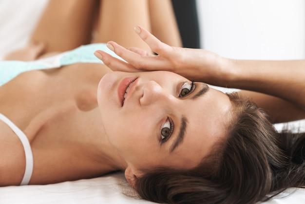 Mulher jovem e bonita caucasiana vestindo lingerie de renda deitada na roupa de cama branca em casa
