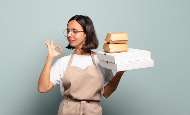 Mulher jovem e bonita chef com recipientes de fast food