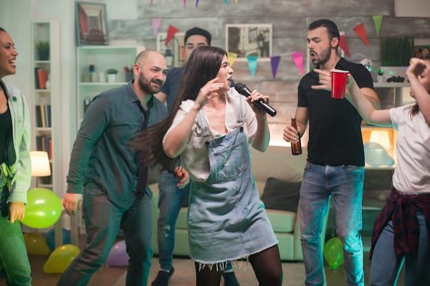 Mulher jovem e bonita cheia de felicidade fazendo karaokê para os amigos na festa.