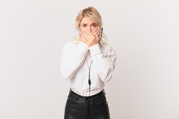 Mulher jovem e bonita cobrindo a boca com as mãos com um choque. conceito de telemarketing