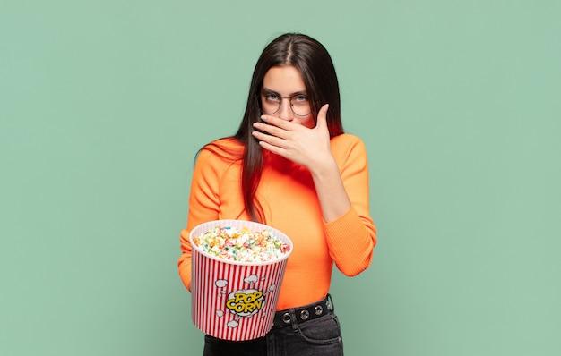 Mulher jovem e bonita cobrindo a boca com as mãos com uma expressão chocada e surpresa, mantendo um segredo ou dizendo oops. conceito de pipocas