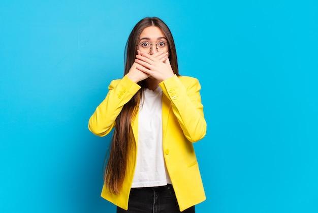 Mulher jovem e bonita cobrindo a boca com as mãos com uma expressão chocada e surpresa, mantendo um segredo ou dizendo oops