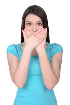 Mulher jovem e bonita cobrindo a boca pelas mãos.