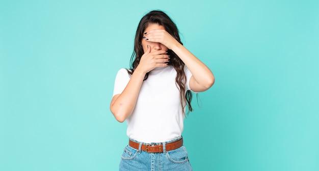 Mulher jovem e bonita cobrindo o rosto com as duas mãos, dizendo não para a câmera! recusando fotos ou proibindo fotos