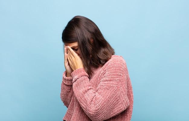 Mulher jovem e bonita cobrindo os olhos com as mãos com um olhar triste e frustrado de desespero, chorando, vista lateral