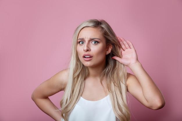 Mulher jovem e bonita coloca a mão na orelha para ouvir melhor em uma parede rosa