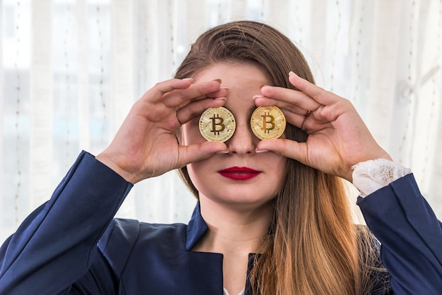Mulher jovem e bonita colocando bitcoins dourados diante dos olhos