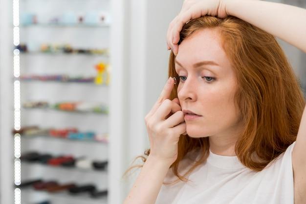Mulher jovem e bonita colocando lente de contato no olho em óptica