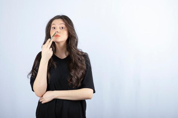 Mulher jovem e bonita colocando o marca-texto com escova cosmética no nariz.