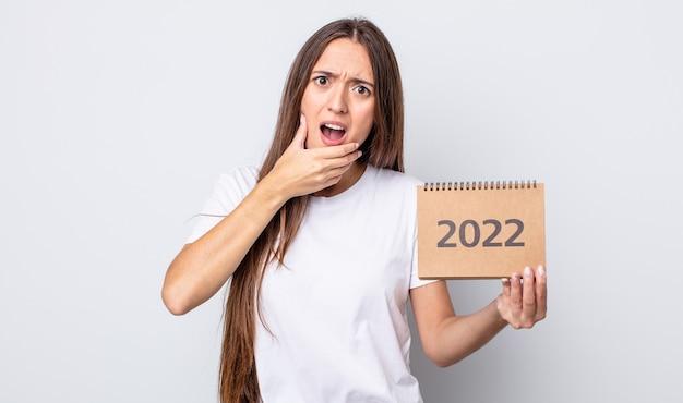 Mulher jovem e bonita com a boca e os olhos bem abertos e a mão no queixo. conceito de planejador 2022
