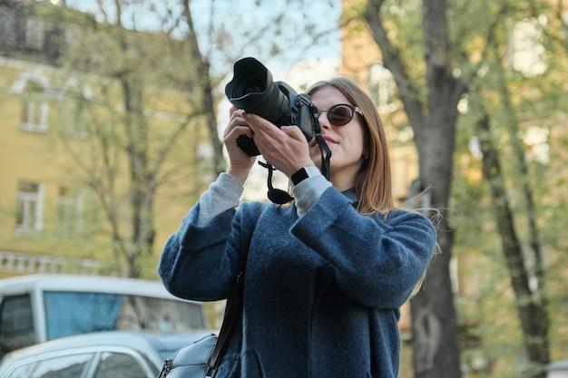 Mulher jovem e bonita com a câmera na cidade.