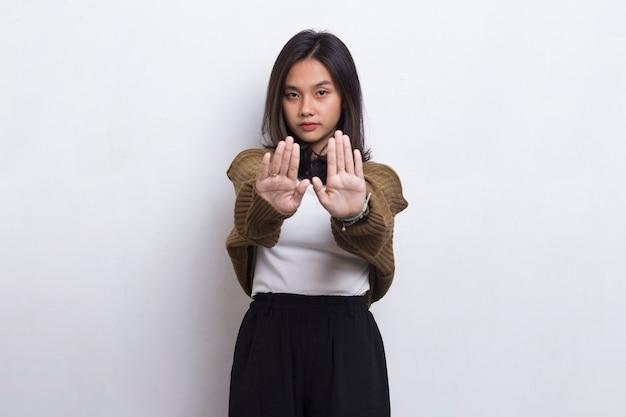 Mulher jovem e bonita com a mão aberta fazendo um sinal de pare com um gesto de defesa de expressão séria