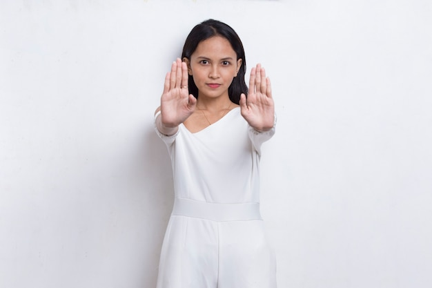 Mulher jovem e bonita com a mão aberta fazendo um sinal de pare com um gesto sério de defesa de expressão