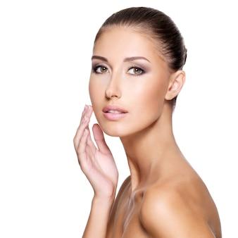 Mulher jovem e bonita com a pele limpa e fresca que toca o rosto com a mão, isolada no branco