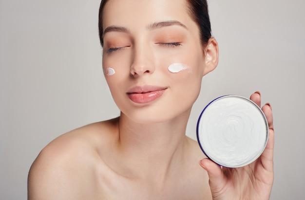 Mulher jovem e bonita com a pele limpa, fresca e olhos fechados, segurando um creme na mão. cosmetologia. conceito de beleza e spa.
