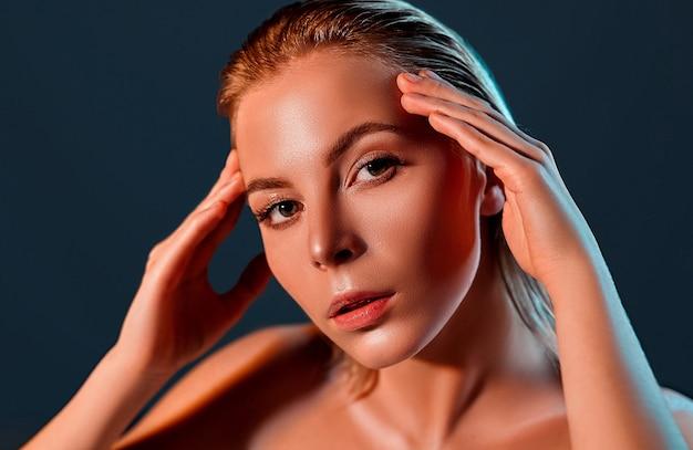 Mulher jovem e bonita com a pele limpa, fresca, tocando seu próprio rosto