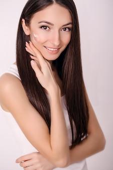 Mulher jovem e bonita com a pele limpa, fresca, toque seu rosto. tratamento facial. cosmetologia, beleza e spa.