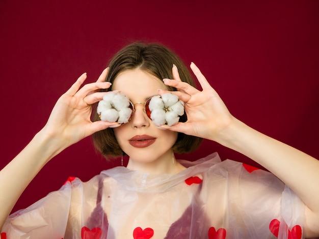 Mulher jovem e bonita com a pele perfeita limpa e grandes lábios posando com flor de algodão nos olhos. retrato do modelo de beleza com maquiagem natural. spa, skincare e bem-estar.