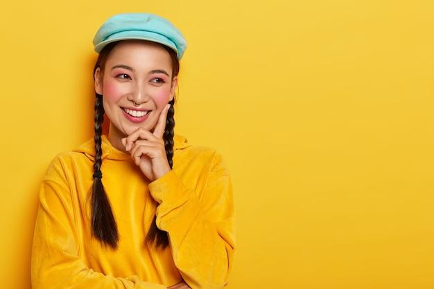 Mulher jovem e bonita com aparência oriental, toca a bochecha rosada com o dedo indicador, olha para o lado, tem sorriso cheio de dentes, vestida com um suéter de veludo brilhante