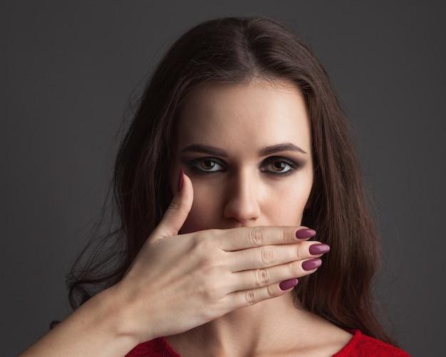Mulher jovem e bonita com as mãos no rosto, cobrindo a boca.