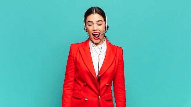 Mulher jovem e bonita com atitude alegre, despreocupada, rebelde, brincando e mostrando a língua, se divertindo