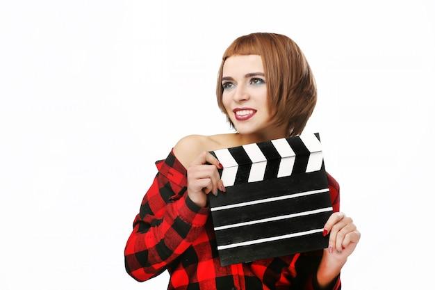 Mulher jovem e bonita com badalo de cinema posando no estúdio