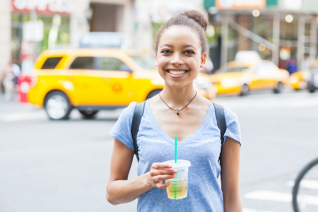 Mulher jovem e bonita com bebida refrescante em nova york