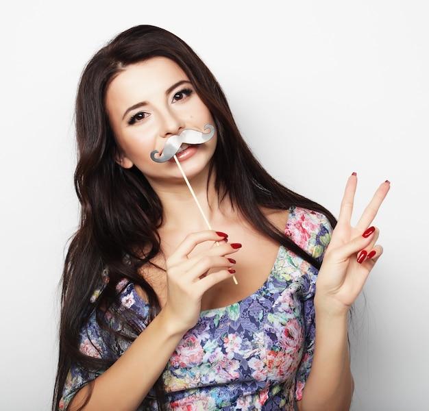 Mulher jovem e bonita com bigodes falsos.
