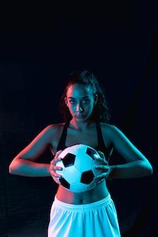Mulher jovem e bonita com bola de futebol