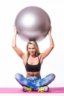 Mulher jovem e bonita com bola de ginástica se exercitando, isolada na parede branca