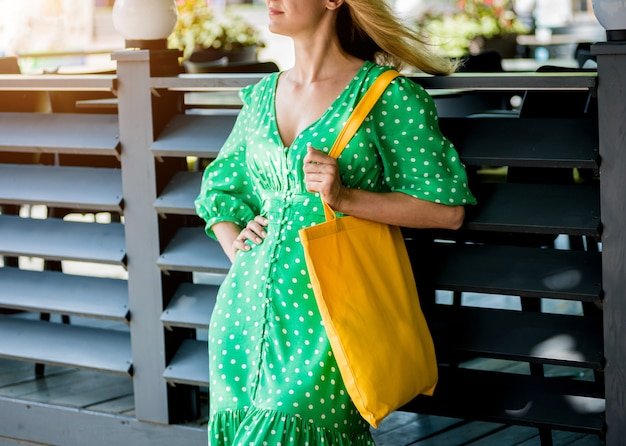 Mulher jovem e bonita com bolsa ecológica de linho amarela no fundo da cidade.