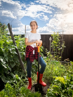 Mulher jovem e bonita com botas de borracha trabalhando no jardim dos fundos