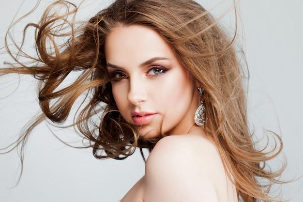 Mulher jovem e bonita com brincos bonitos, close-up do retrato. cabelo voador