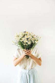 Mulher jovem e bonita com buquê de flores de camomila branca