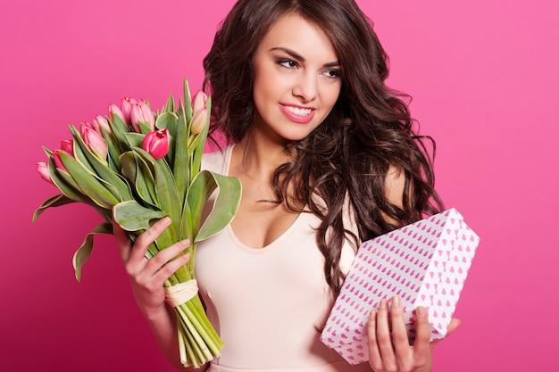 Mulher jovem e bonita com buquê de primavera e caixa de presente