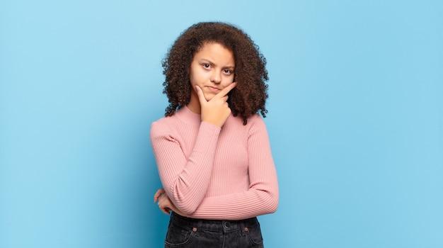 Mulher jovem e bonita com cabelo afro e suéter rosa posando na parede azul