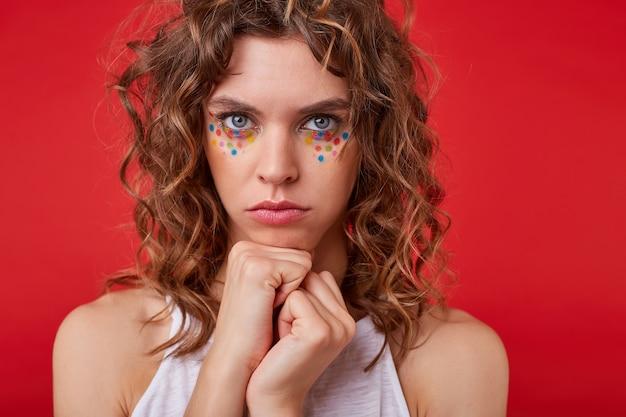 Mulher jovem e bonita com cabelo cacheado castanho claro em pé, parecendo ofendida e confusa, cerrando os punhos perto do rosto