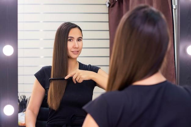 Mulher jovem e bonita com cabelo castanho comprido e liso cuida do cabelo. penteando o cabelo e se olhando no espelho