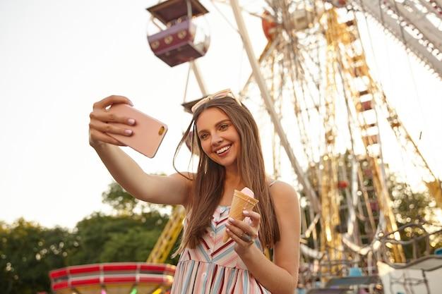 Mulher jovem e bonita com cabelo castanho posando sobre a roda gigante em um dia ensolarado e quente, usando óculos escuros e um vestido romântico, sorrindo alegremente enquanto faz selfie com o smartphone