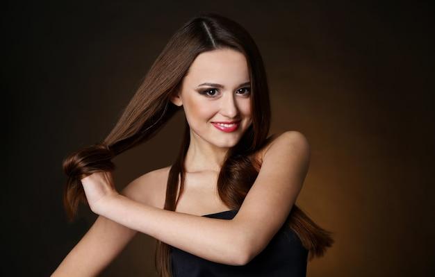 Mulher jovem e bonita com cabelo comprido em fundo marrom escuro