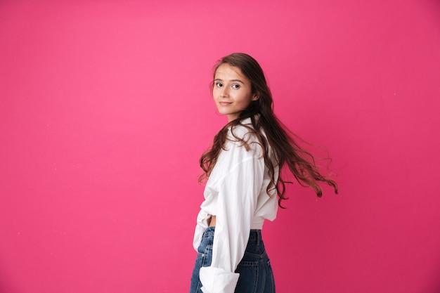 Mulher jovem e bonita com cabelo comprido encaracolado em pé e olhando para a frente, isolado na parede rosa