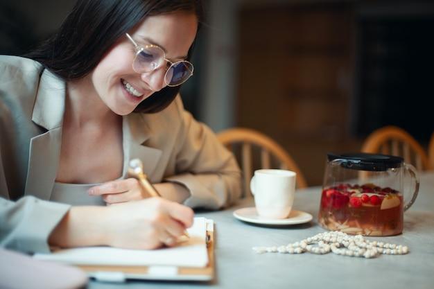 Mulher jovem e bonita com cabelo comprido escuro em um terno escrevendo seus planos de negócios no diário enquanto bebe café no intervalo. conceito de planejamento e gerenciamento de tempo. aprendendo com atitude positiva.