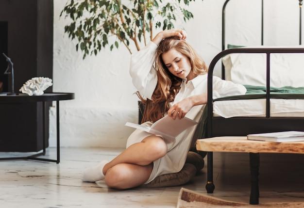Mulher jovem e bonita com cabelo comprido lendo um livro sentada no quarto com lençóis brancos