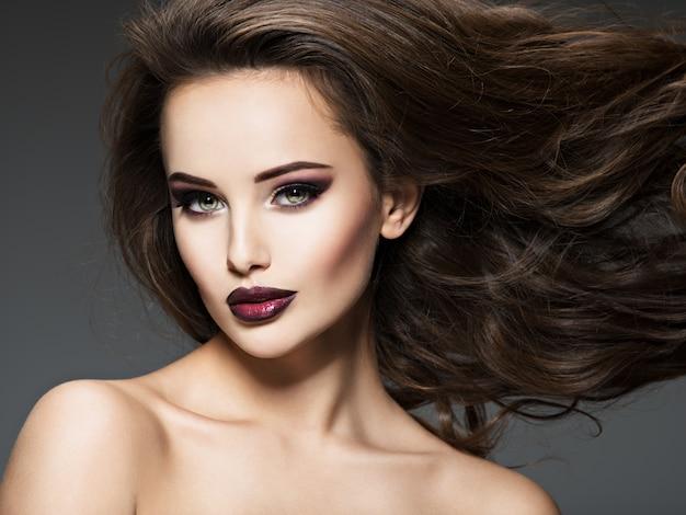 Mulher jovem e bonita com cabelo comprido. retrato de uma garota incrível com maquiagem de moda de estilo.
