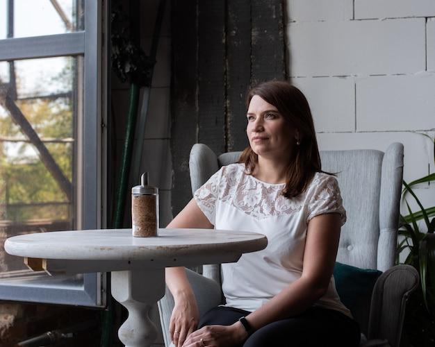 Mulher jovem e bonita com cabelo comprido ruivo em uma blusa branca, sentada sozinha em um café esperando seu pedido.